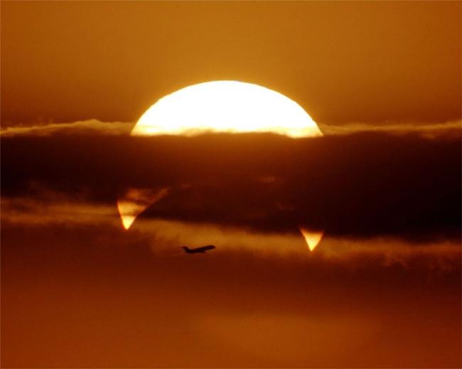 2706155-R3L8T8D-650-airplaine-crosses-partial-solar-eclipse