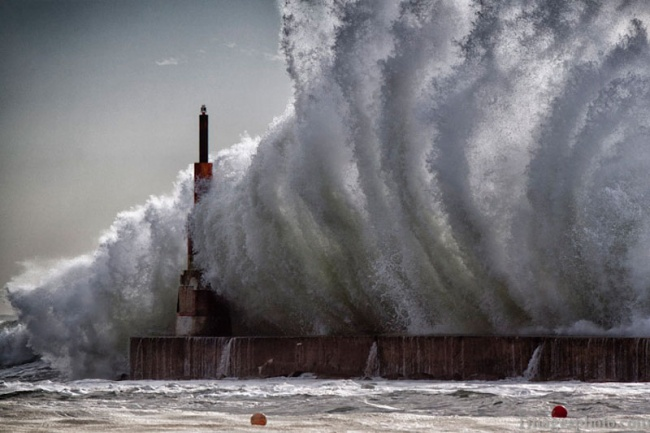 2698655-R3L8T8D-650-crashing-waves-into-lighthouse-pier-gaia-portugal